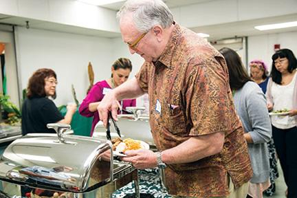 Chancellor Doug Dykstra samples the teriyaki chicken with pineapple chunks – Carolynn Yamada